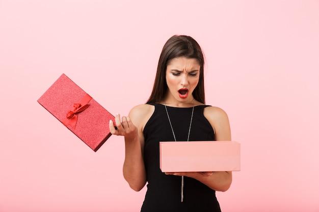 Verstoorde vrouw die zwarte kleding draagt die lege giftdoos houdt die over roze achtergrond wordt geïsoleerd