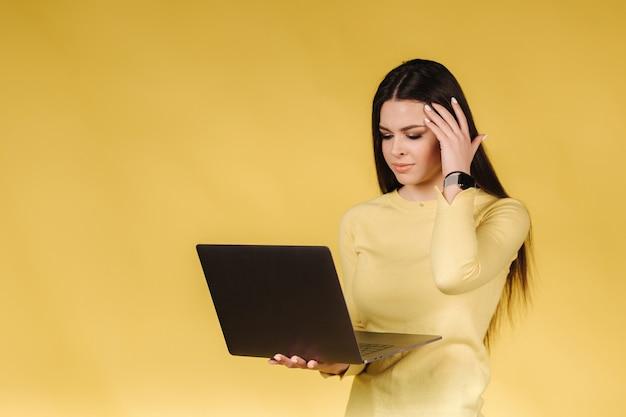 Verstoorde vrouw in geel sweatshirt houdt laptop vast en hief haar hand op om naar het hoofd te gaan