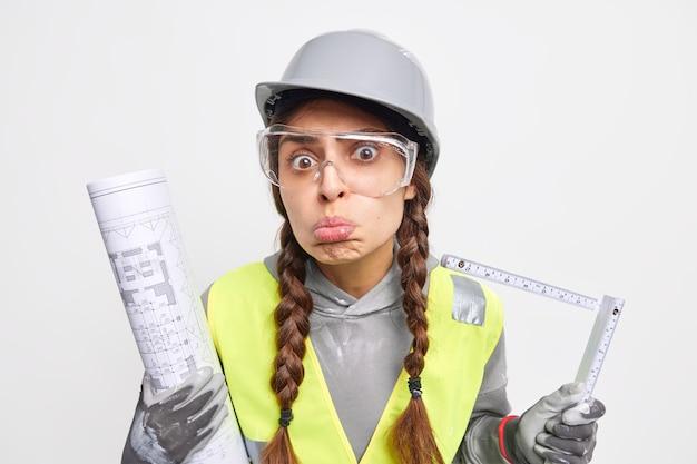 Verstoorde vrouw ingenieur maakt grimas gebruikt meetlint op bouwplaats houdt papieren blauwdruk betrokken bij appartement repai kijkt droevig naar camera