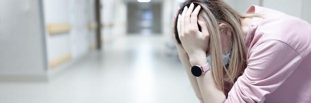 Verstoorde vrouw met beschermend medisch masker zit in ziekenhuisgang