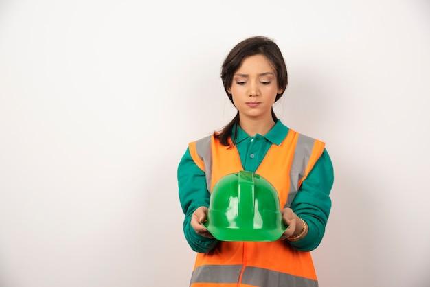 Verstoorde vrouwelijke ingenieur die een helm op witte achtergrond houdt.