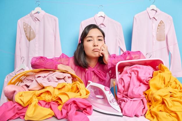 Verstoorde wasserijmedewerker leunt tegen manden vol linnen en voelt zich moe druk bezig met strijken poses tegen blauwe muur