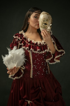 Verstoppen met masker. portret van middeleeuwse jonge vrouw in rode vintage kleding die zich op donkere achtergrond bevindt. vrouwelijk model als hertogin, koninklijk persoon. concept vergelijking van tijdperken, modern, mode, schoonheid.