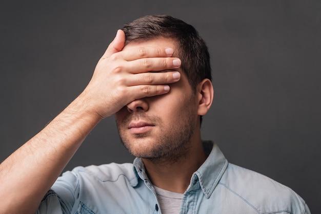 Verstoppertje! jonge knappe man die zijn ogen bedekt met zijn hand terwijl hij tegen een grijze achtergrond staat