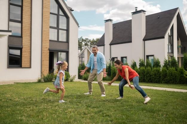 Verstoppertje. ouders en dochter voelen zich vrolijk tijdens het verstoppertje spelen buiten in de buurt van huis