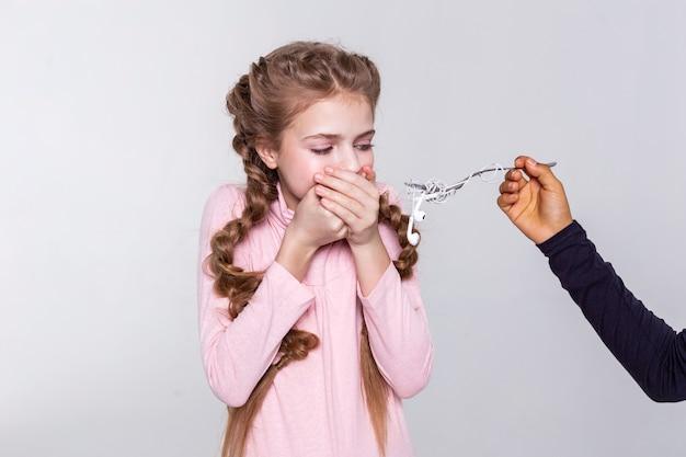 Verstrikte koptelefoon. blond jong meisje walgt van de voorgestelde maaltijd en bedekt haar mond stevig