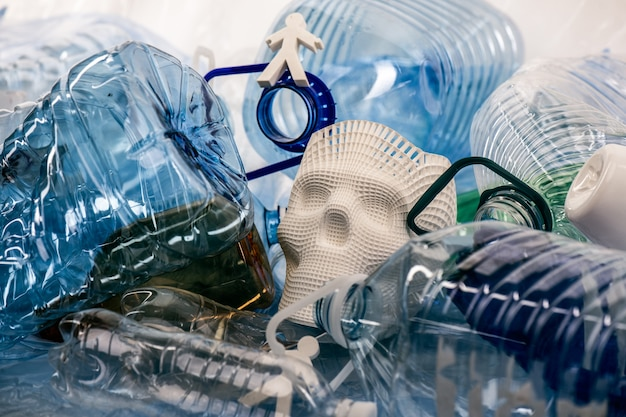 Vertegenwoordigend probleem. plastic modellen van mensen en schedels die in een stapel plastic afval liggen en de toestand van onze planeet voorstellen