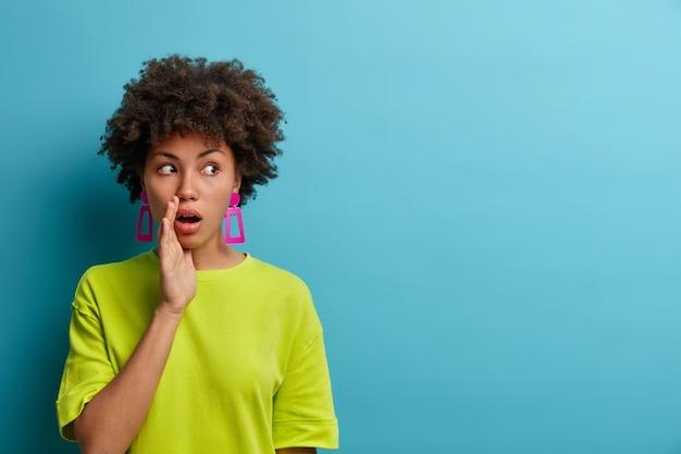 Vertel het aan niemand! geschokte spraakzame jonge vrouw houdt handpalm bij de mond, kijkt opzij, vertelt privé-informatie en verspreidt geruchten, onder de indruk van verrast plotseling nieuws, geïsoleerd op blauwe muur