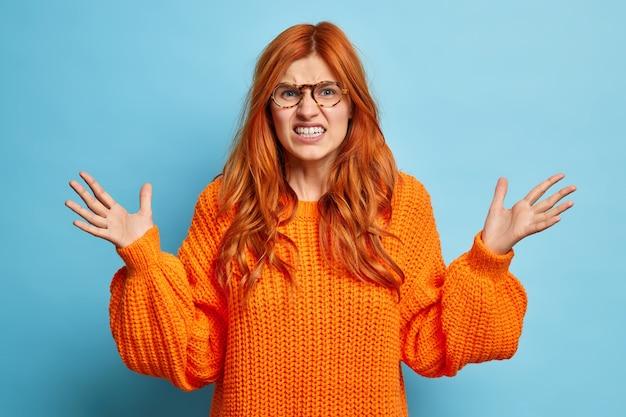 Vertel me niet over deze onzin. geërgerd jonge roodharige vrouw klemt haar tanden, fronst gezicht en steekt boos handpalmen op uit irritatie draagt gebreide trui.