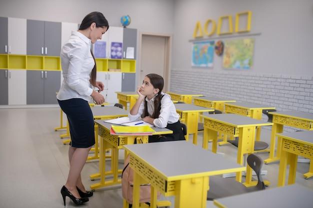 Vertellende leraar in witte blouse en donkere rok en aandachtig luisteren schoolmeisje zit aan bureau in de klas