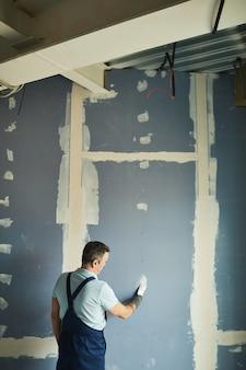 Verticaal achteraanzicht portret van senior man aan het werk op droge muur tijdens het renoveren van huis, kopieer ruimte