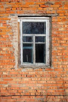 Verticaal bakstenen muur met een raam in een oud rustiek frame.