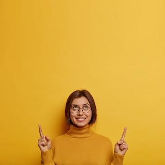 Verticaal beeld van aantrekkelijke glimlachende vrouw wijst wijsvinger naar boven, schept op over haar nieuwe plafond, draagt een losse coltrui