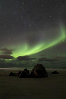 Verticaal beeld van adembenemend noorderlichtfenomeen in de atlantische oceaan tegen een sterrenhemel
