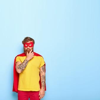 Verticaal beeld van bedachtzame superheld denkt hoe hij iets aardigs voor iemand kan doen, wil iets goeds maken