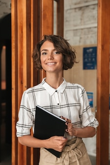 Verticaal beeld van bedrijfsvrouw met in hand omslag