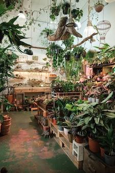 Verticaal beeld van bloemenwinkel met grote aantallen verschillende bloemen en planten in potten op de planken