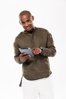 Verticaal beeld van de gelukkige afrikaanse mens die tabletcomputer en het kijken gebruiken