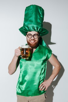 Verticaal beeld van de glimlachende mens in st.patriks-kostuum dat bier houdt