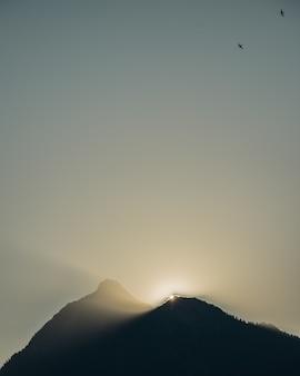 Verticaal beeld van de silhouetten van heuvels onder het zonlicht tijdens de zonsondergang