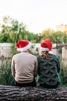 Verticaal beeld van een achteruitkijkpaar dat kerstmutsen draagt met kerstmis in 2021. concept van reünie en kijkend naar de toekomst.