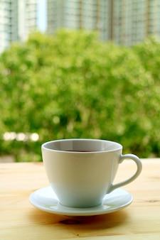 Verticaal beeld van een kop van hete thee op de venster zij houten lijst