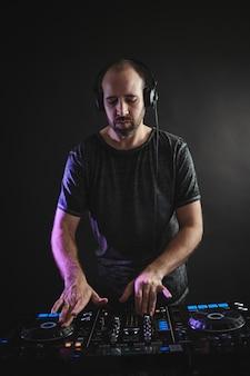 Verticaal beeld van een mannelijke dj die onder de lichten tegen donker in een studio werkt