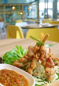 Verticaal beeld van gegrilde kip bbq met pittige saus geserveerd op de houten tafel van het restaurant