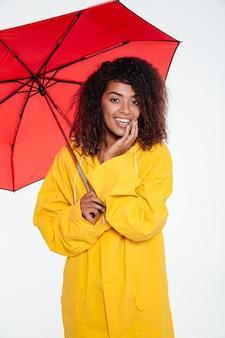 Verticaal beeld van gelukkige afrikaanse vrouw in regenjas het stellen