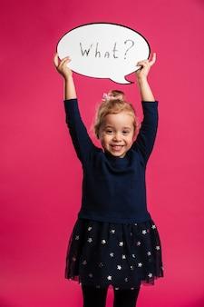 Verticaal beeld van gelukkige jonge blonde meisjesholding toespraakbel wat en bekijkend de camera over roze muur