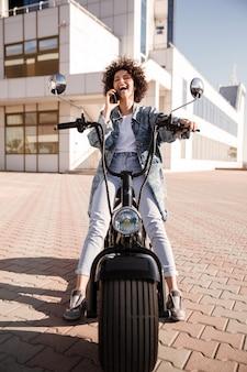 Verticaal beeld van gelukkige krullende vrouwenzitting op moderne motor