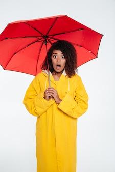 Verticaal beeld van geschokte afrikaanse vrouw in regenjas het stellen