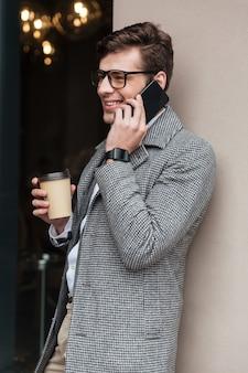 Verticaal beeld van glimlachende zakenman in oogglazen en laag