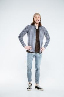 Verticaal beeld van het glimlachen hipster met armen op heup