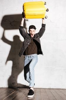 Verticaal beeld van hipster in snapback die koffer boven houdt