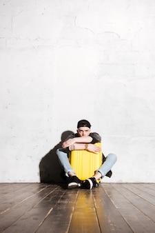 Verticaal beeld van hipster in snapback knuffelkoffer