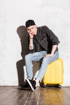 Verticaal beeld van hipster in teruggeklap zittend op koffer