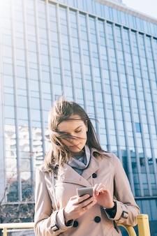 Verticaal beeld van jonge donkerbruine vrouw die in beige laag mobiele telefoon bij de high-rise bouw bekijken