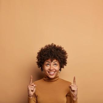 Verticaal beeld van knappe afro-amerikaanse vrouw met krullend kapsel, grijpt uw aandacht naar iets naar boven, helpt bij het nemen van een betere winkelbeslissing, terloops gekleed, vormt over beige muur