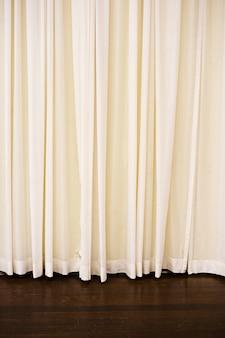 Verticaal beeld van lichte gordijnen die boven de vloer onder de lichten hangen