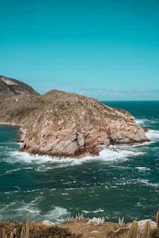 Verticaal beeld van rotsen bedekt met groen omgeven door de zee in rio de janeiro