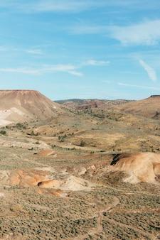 Verticaal beeld van rotsen bedekt met zand en groen onder zonlicht en een blauwe hemel