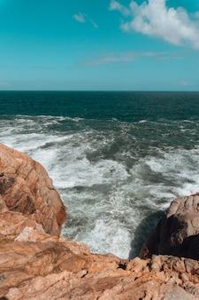 Verticaal beeld van rotsen omgeven door de zee onder een blauwe lucht en zonlicht