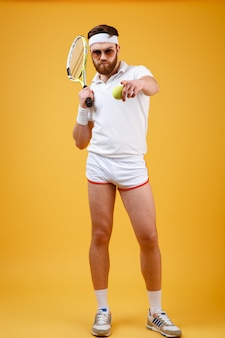 Verticaal beeld van sportman met tennisracket het richten
