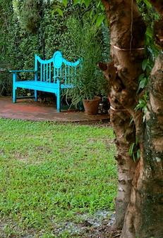 Verticaal beeld van turquoise blauwe houten bank in de zomertuin