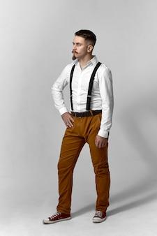 Verticaal beeld van volledige lengte van modieuze hipster kerel die kleding krijgt