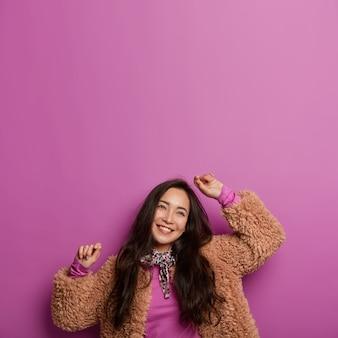 Verticaal beeld van vrolijke gelukkige koreaanse vrouw met lang donker haar, kantelt het hoofd en houdt de armen omhoog, heeft dromerige uitdrukkingen