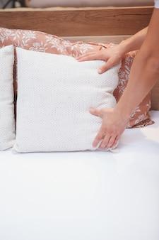 Verticaal bijgesneden schot van mannelijke armen die een bed maken