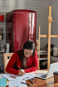 Verticaal binnenschot van vrouw maakt financieel verslag, vormt bij gezellige keuken met koelkast op achtergrond.