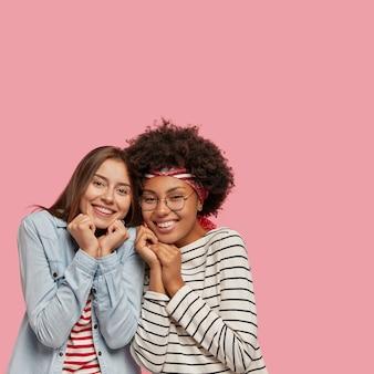 Verticaal binnenshuis shot van prettig ogende vrolijke halfbloedzussen die steun van elkaar voelen